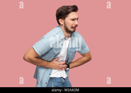 Stomach pain. Portrait of sick sad handsome bearded young man in blue casual style shirt standing and holding his painful belly. indoor studio shot, i - Stock Image