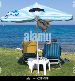Two people relaxing under an umbrella by the sea - Stock Image
