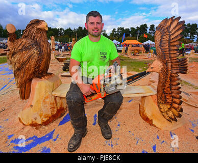 UK competitor Mike Burgess with the pair of Eagles carved out of a block of pine timber at the Carrbridge Chainsaw Championship event in 2018. - Stock Image