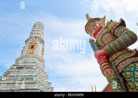 Yaksha statue in the Grand Palace in Bangkok, Thailand, with white pagoda in the background. The demon-gods statues are a common sight in Buddhist tem - Stock Image