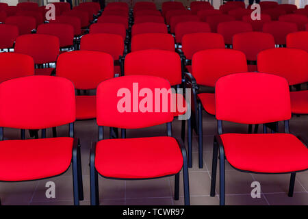 Conference room with a red stage and red chairs for events, conferences and seminars - Stock Image