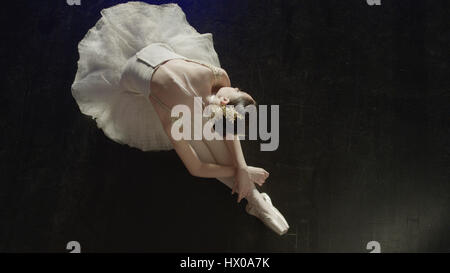 High angle view of performing dancer ballerina in tutu and toe shoes laying gracefully on stage floor - Stock Image