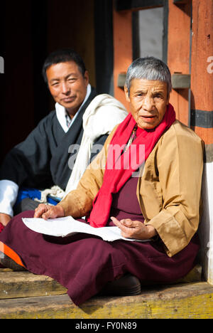 Elderly Vajrayana Buddhist nun in crimson robe and Bhutanese man in traditional gho sitting on terrace at Paro Dzong, - Stock Image