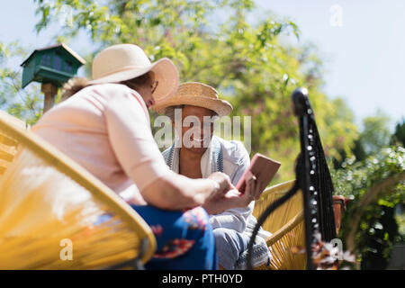 Senior women friends using smart phone on sunny patio - Stock Image