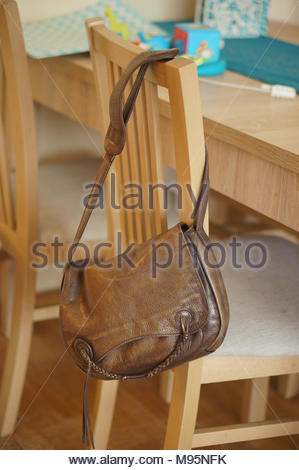 Women leather bag hanging on a wooden chair - Stock Image
