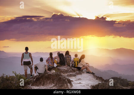 Big group of friends stands on mountain top and looks at beautiful sunset. Travel with friends concept - Stock Image