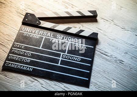 Vintage film clapper on wooden desk. Filmmakers equipment background - Stock Image
