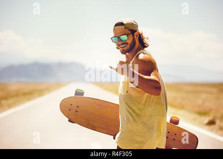 Happy athletic man walks with skateboard or longboard by straight road - Stock Image