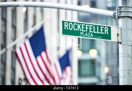 (Selective focus) Close-up view of green road sign depicting 'Rockefeller Plaza' in Midtown Manhattan, New York City. - Stock Image