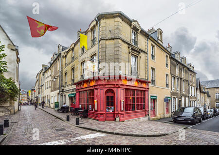 The colorful red facade front of a restaurant on a corner intersection in the Normandy town of Bayeux France with - Stock Image