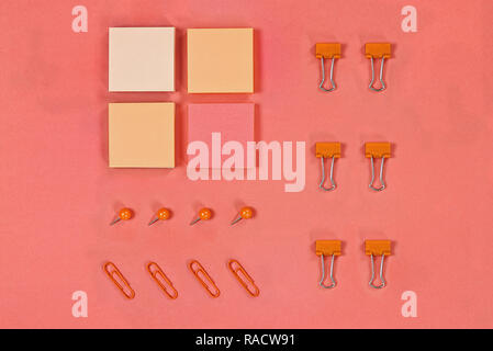 Variety of note pad paper, push pins and paper clips for organizing over coral color background with free space for text. Image shot from above. - Stock Image