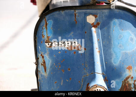 An old, rusty, well used Vespa scooter. The picture clearly shows the distinctive Vespa badge highlighted against - Stock Image