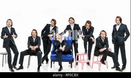 The eight identical handsome men in  black suits differently pose on a white background, brutal man with long curly hairs, white shirts, business man - Stock Image