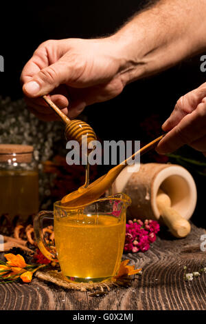 Honey. Hand with dipper picking honey from a jar of honey - Stock Image
