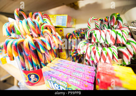 Bright rainbow-coloured traditional candy sticks on a packed sweet shop shelf in The Guildhall Bath, UK - Stock Image