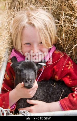 Blond girl holding black lamb. - Stock Image