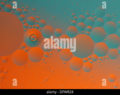 Abstract oil droplets in water with a contrasting blue and orange background. - Stock Image
