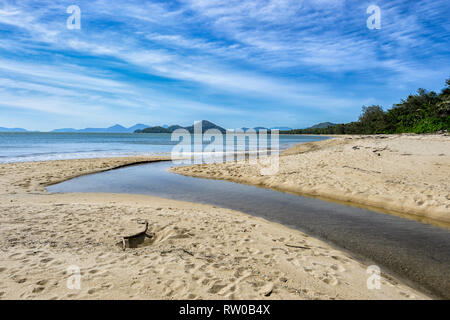 Creek flowing into the sea during the wet season, Palm Cove, Far North Queensland, QLD, FNQ, Australia - Stock Image