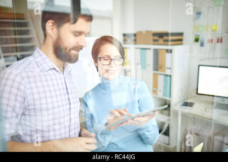 Young banker pointing at touchpad screen while making presentation of upgraded online data to colleague in office - Stock Image