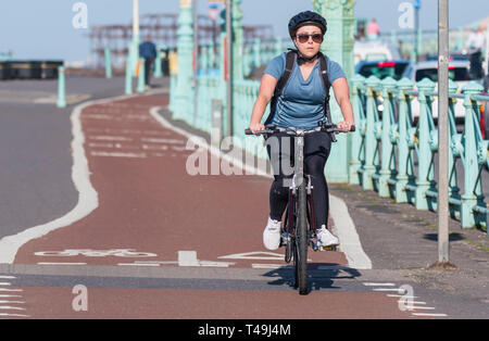 Young woman wearing a helmet riding a bicycle in a cycle lane in Brighton, East Sussex, England, UK. - Stock Image