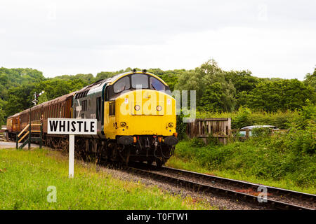Restored British Rail Class 37 diesel engine 37264 of the North Yorkshire Moors Railway passing whistle sign outside Pickering, North Yorkshirem Engla - Stock Image