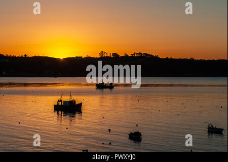 Schull, West Cork, Ireland. 18th Oct, 2018. The sun peers over the horizon in Schull Harbour. The day will be dry and bright with sunny spells and temperatures of 11 to 14°C. Credit: Andy Gibson/Alamy Live News. - Stock Image