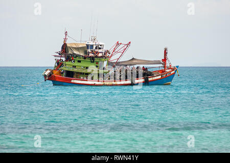 Traditional large scale industrial fishing boat with crew on deck in calm tropical waters. - Stock Image