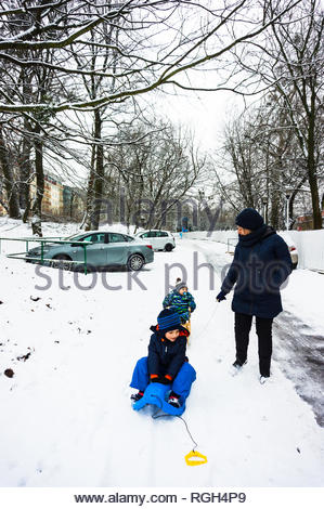 Poznan, Poland - January 26, 2019: Woman and two children on a sled on a footpath covered with snow at a park on a cold winter day. - Stock Image