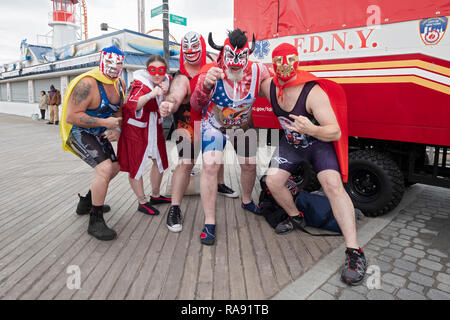 4 men and a woman dressed as wrestlers prior to the annual Polar Bear Club New Year's day swim in Coney Island, NYC. - Stock Image