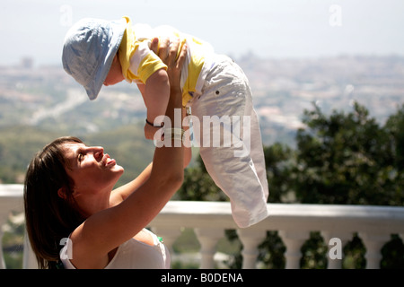 Young woman holding toddler over her head at Mijas Pueblo, Costa del Sol, Andalucia, Spain - Stock Image