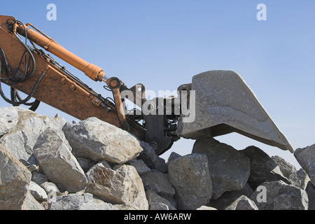 Diggers scoop resting on rocks - Stock Image