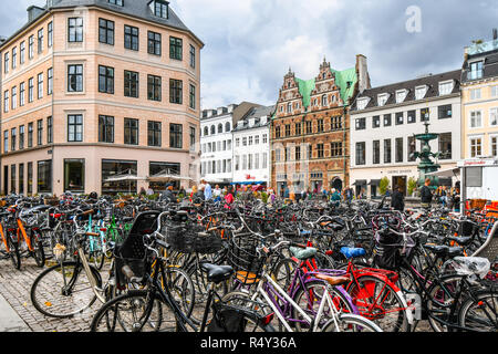 Bicycles parked alongside the Stroget shopping district, the longest pedestrian street in the world, in the historic center of Copenhagen, Denmark. - Stock Image