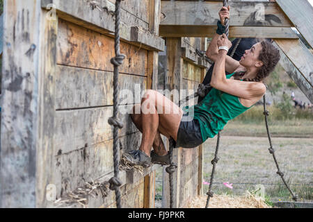 Fit young 19 year old woman competitor climbing an obstacle in an 8km obstacle course challenge - Stock Image