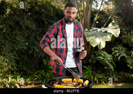 A man holding a beer and barbecuing vegetables - Stock Image