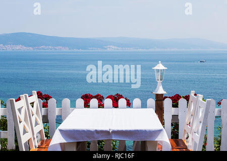 romantic dinner white tablecloth white chairs on the background of the sea . - Stock Image