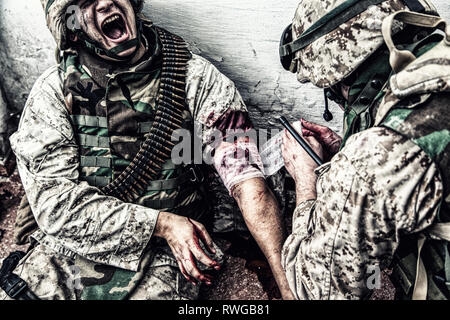 Marine suffering in pain while a military medic applies a bandage to gunshot wound. - Stock Image