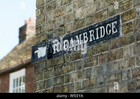 Old style design hand and finger street road traffic sign on a brick wall pointing to Cambridge. - Stock Image