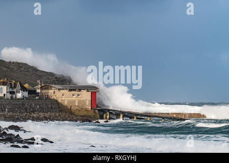 Sennen, Cornwall, UK. 10th March 2019. UK Weather. Winds in excess of 50 mph and huge waves battered Sennen Cove, near to lands end,  this morning. Credit: Simon Maycock/Alamy Live News - Stock Image