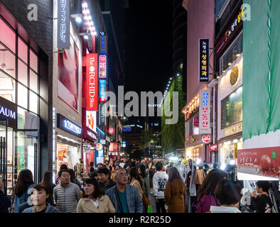 Streets of Myeongdong in Seoul, South Korea busy with shoppers and tourists at night.  Lights from shops and shop signs light up the street - Stock Image