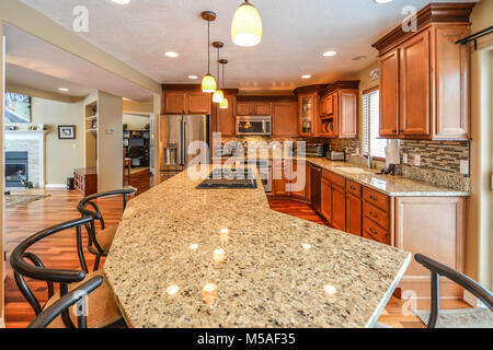 Spacious upscale kitchen in a luxury home with large granite slab center island with bar stools, granite counters - Stock Image