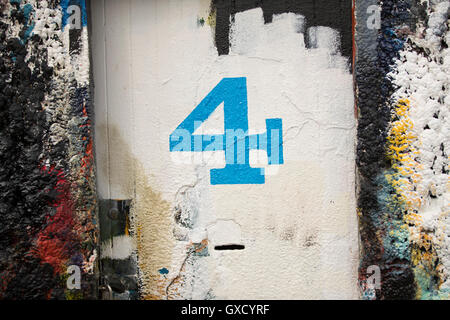 Number 4 door and paint covered wall in ship painters yard - Stock Image