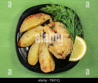 Still-life with fried fish and baked potatoes on a platter - Stock Image