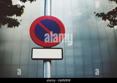 'No parking' road sign with blank frame for your text placed on metal street lantern, blurred tiled facade - Stock Image