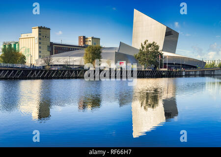 November 2 2018: Salford Quays, Manchester, UK - Imperial War Museum North, reflected in the deep blue water of the Manchester Ship Canal, on a beauti - Stock Image