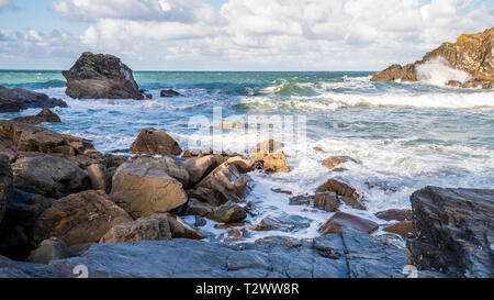 A fresh bright and breezy day in a quiet rocky cove on the North Cornish coast with waves and surf. - Stock Image