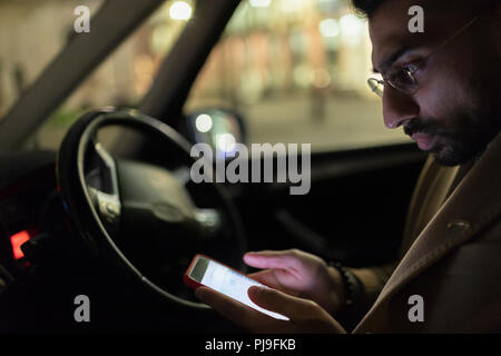 Man using smart phone in car at night - Stock Image