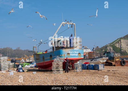 Hastings fishermen load cuttlefish nets ready for sea, on the Old Town Stade fishing boat beach. Hastings has the largest beach-launched commercial fishing fleet in Britain, East Sussex, UK - Stock Image