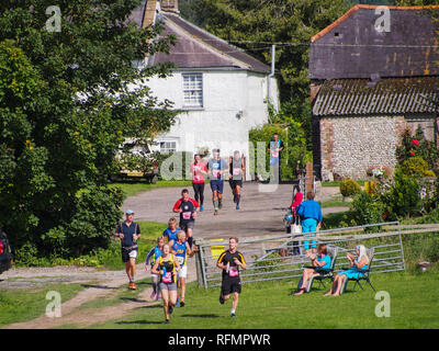 Runners running through a farm yard during a trail running race - Stock Image