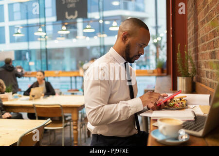 Businessman using smart phone and eating lunch in cafe - Stock Image