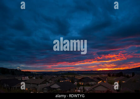 A colorful sky at sunset looking out over an American subdivision in the Pacific Northwest. - Stock Image